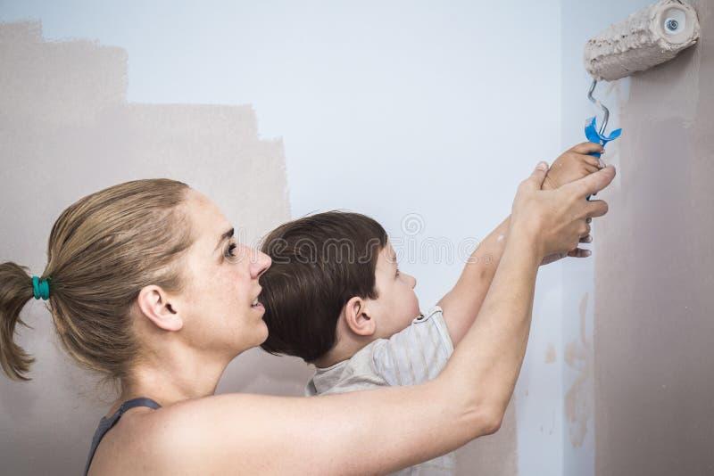 Teachs de la mam? sus 3 a?os de pintura del hijo con el rodillo en casa imagenes de archivo