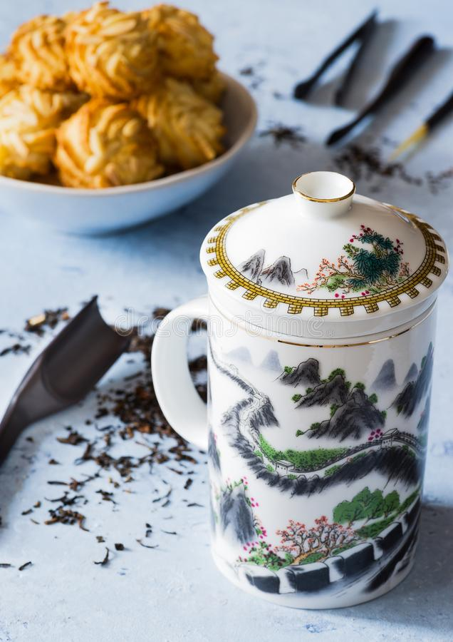 A teacup with 'Great wall' design, biscuits, tea, on delicate background. A teacup with 'Great wall' design, some biscuits, tea, on royalty free stock images