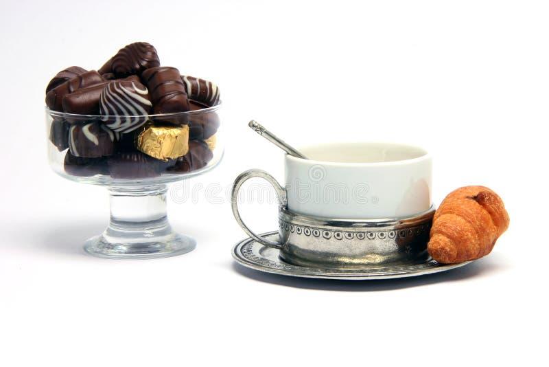 Teacup croisant chocolates. Chocolate teacup and croisant isolated on white background stock photos