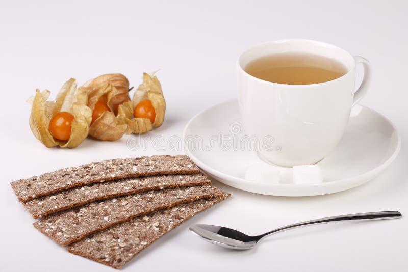 Teacup med den ryekornbröd och physalisen royaltyfri foto