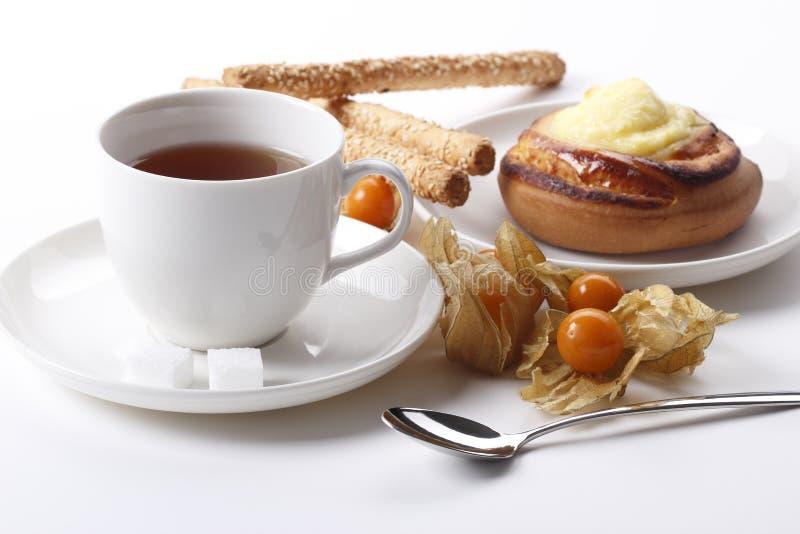 Teacup med ostkaka, kakor och physalisen royaltyfri fotografi