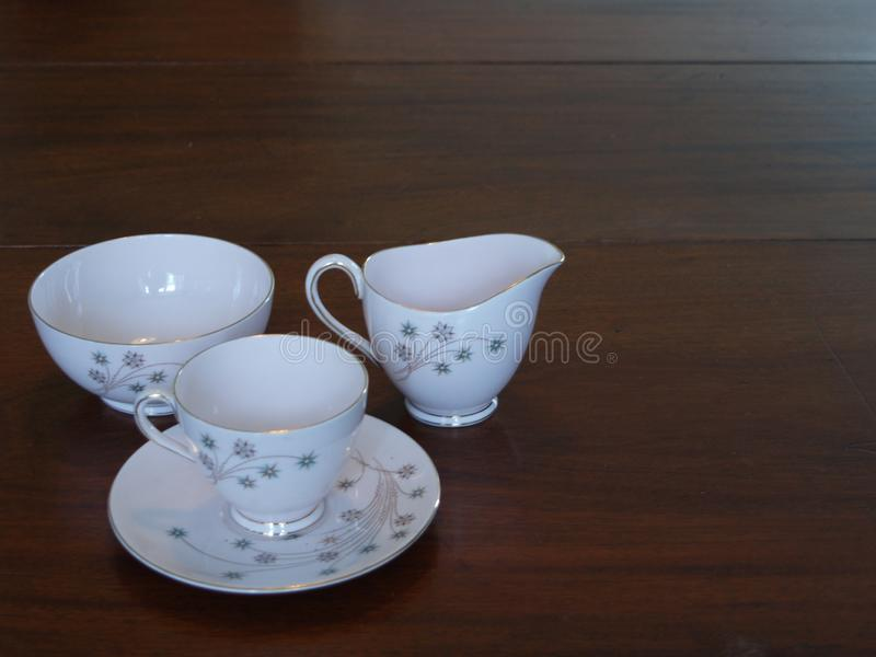 Vintage tea set on mahogany dining table. Teacup, milk jug and sugar bowl in pink with gilt decoration royalty free stock image