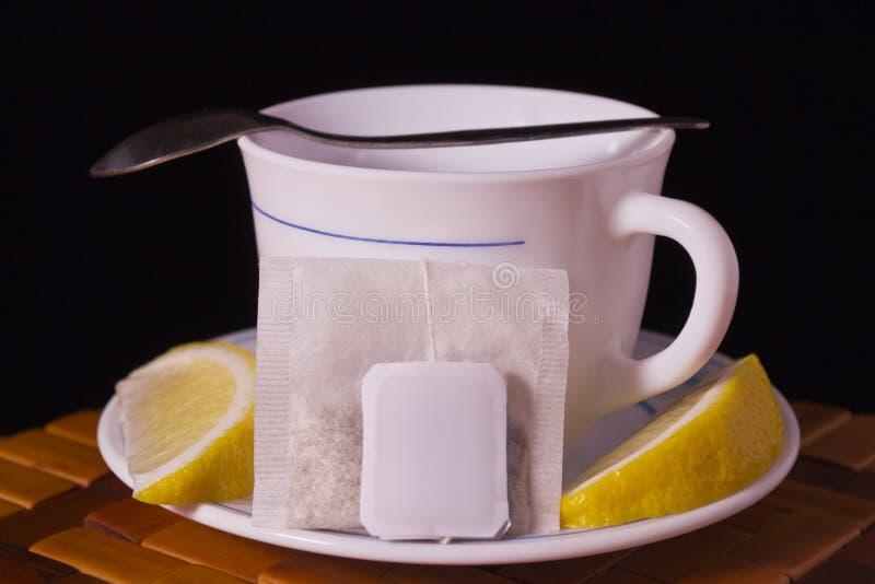 Teacup och citron med tea och lite skeden arkivfoton