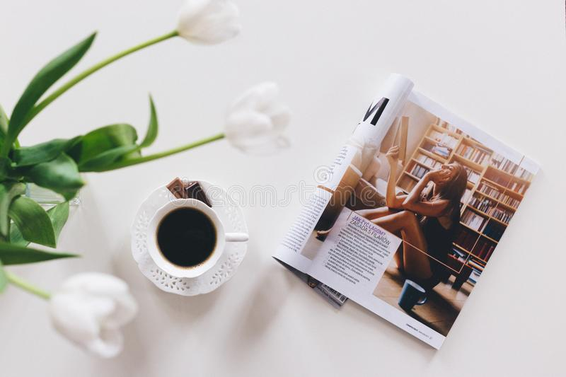 1 Teacup With Saucer and Magazine on White Surface stock images