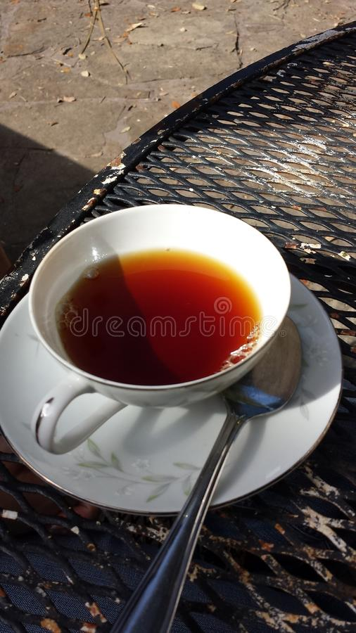 Teacup with spoon on porch table stock photography