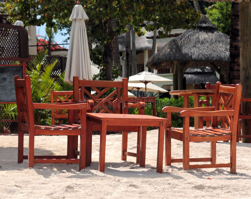 Teak furniture. Set on sand by the beach stock photo