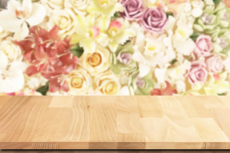 Teak wood table top with colorful roses flowers background. royalty free stock photography