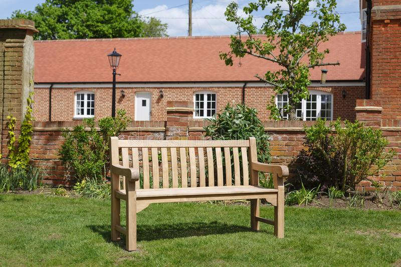 Teak wooden garden bench. Teak hardwood bench on a lawn in an English garden with historic Victorian home in the background stock photos
