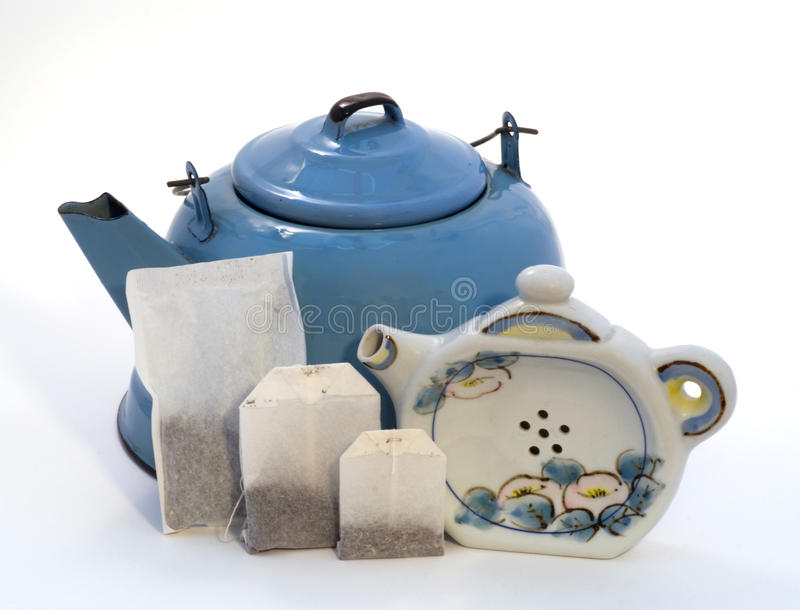 Teakettle, tea bags, & teapot shape teabag holder. 3 sizes of teabags leaning against a vintage blue enamel teakettle. A special teabag holder in the shape of a stock photo
