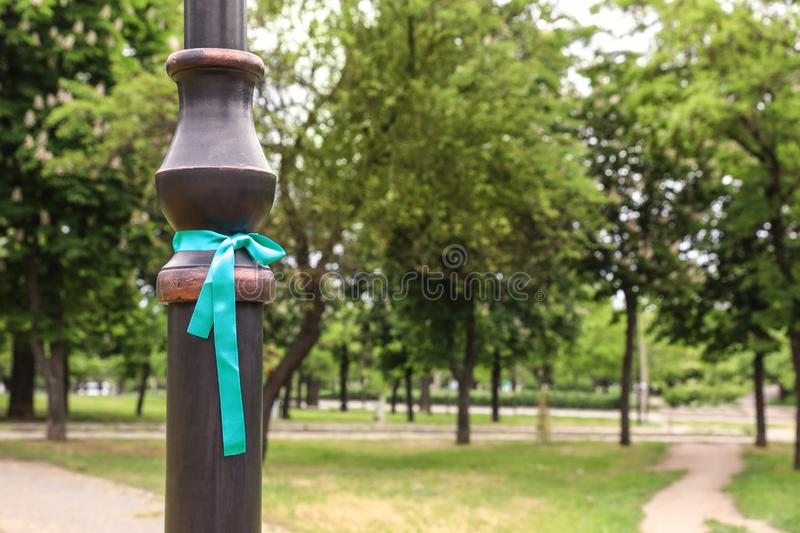 Teal awareness ribbon tied on lamppost in park. Space for text royalty free stock photo