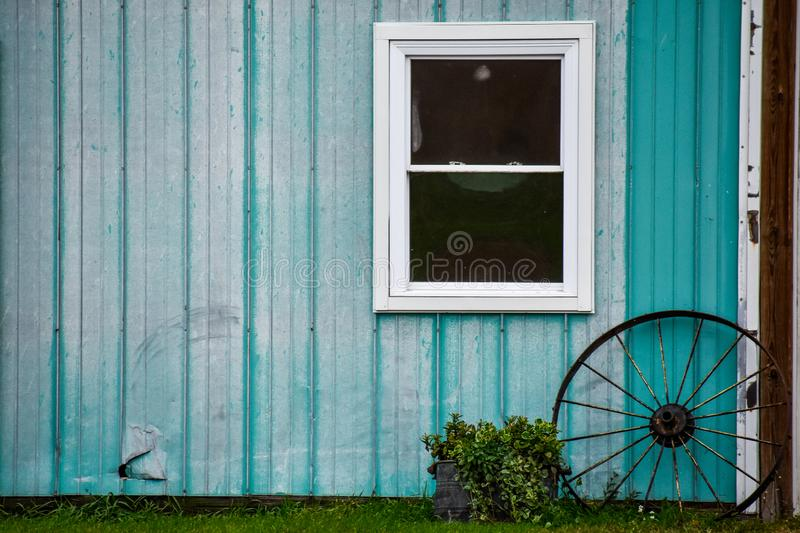 Teal barn with wagon wheel window and flower kettle planter hole in siding. Teal siding on a barn with a window and a metal wagon wheel leaning against it and a royalty free stock images