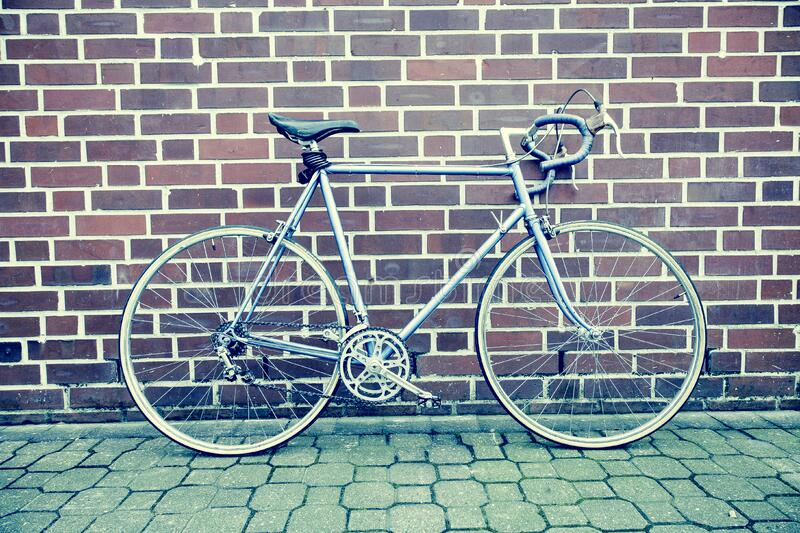 Teal and Black Road Bike Near Black and Brown Brick Wall stock image