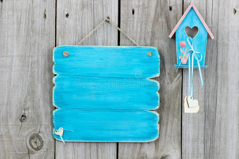 Teal blue blank sign next to blue and pink birdhouse hanging on fence stock photography