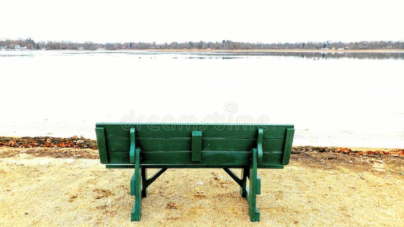 Teal Park Bench In Front of Lake stock photography