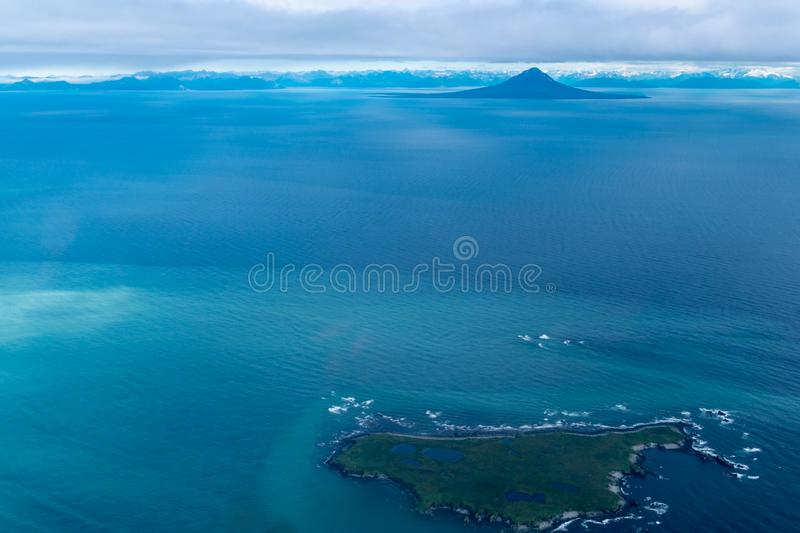 Teal waters of Alaska near Katmai National Park, with view of Augustine Island and the Aleutian Range of mountains. Aerial stock image