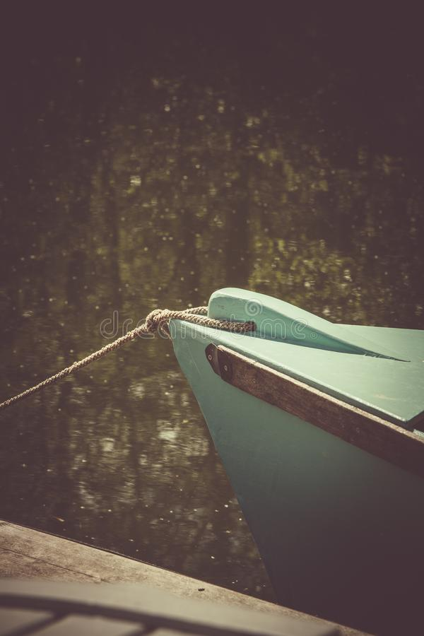 Teal Wooden Boat on Lake stock photo