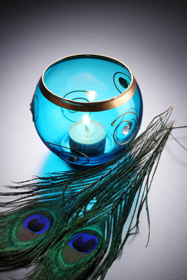 Tealight. Blue round tealight wit peacock feather royalty free stock images