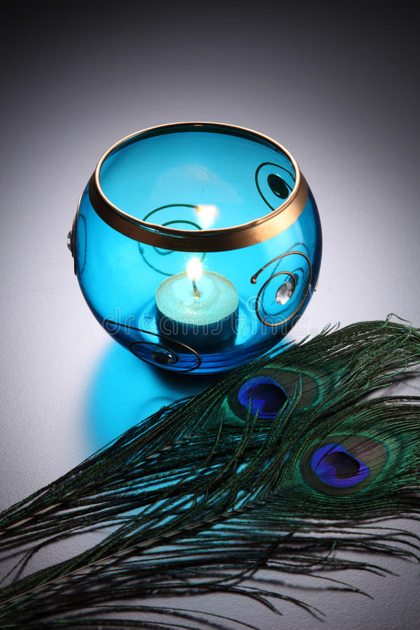 Tealight. Blue round tealight wit peacock feather stock photos