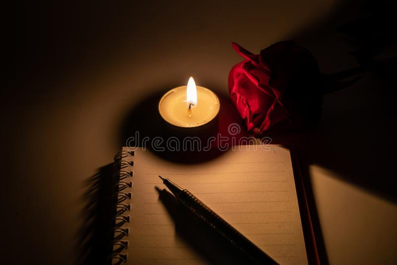Tealight candle, pen, note book and roses. At midnight time royalty free stock photo