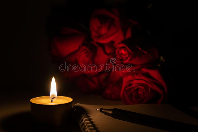 Tealight candle, pen, note book and roses. At midnight time stock photo