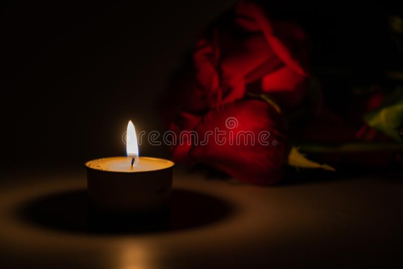 Tealight candle and red rose at midnight. Time stock photo