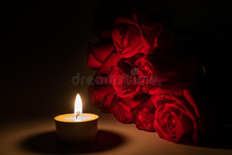 Tealight candle and red rose at midnight. Time stock photography