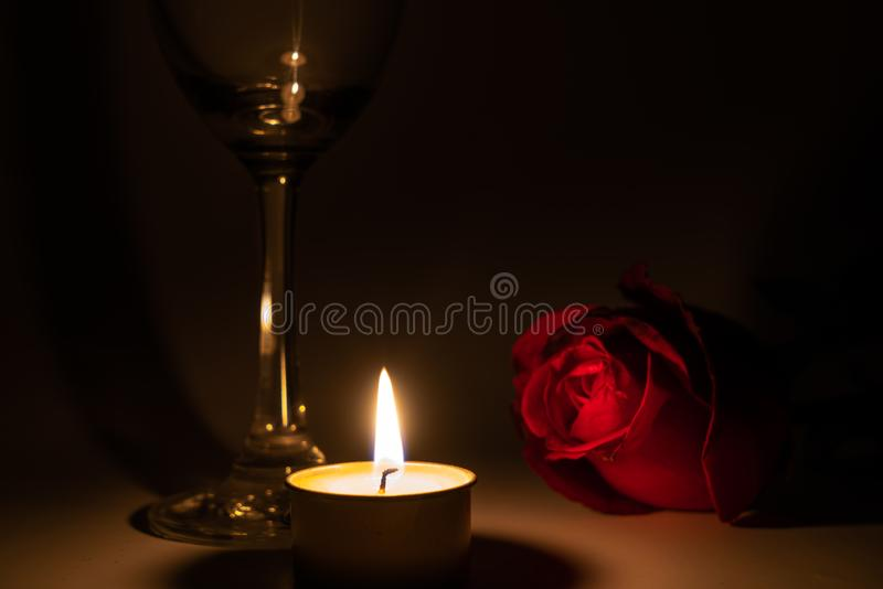 Tealight candle, wine glass and rose. In the dark night royalty free stock photography
