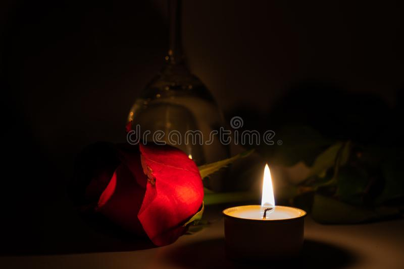 Tealight candle, wine glass and rose. In the dark night royalty free stock photos