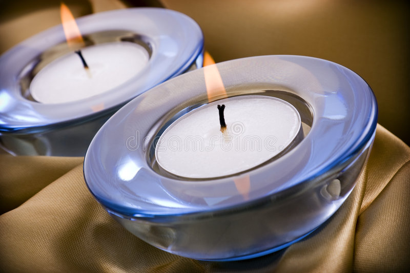 Tealight candles. On a gold satin textile background royalty free stock photography