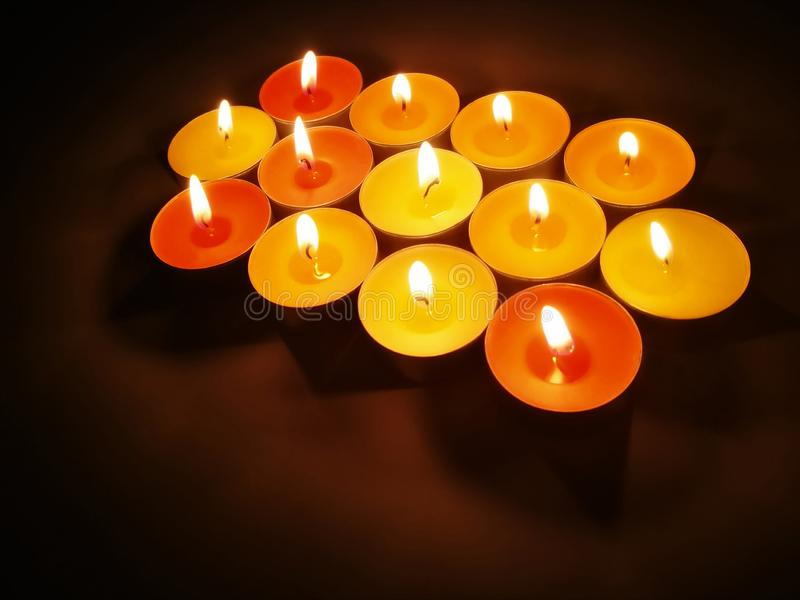 Tealight candles with blurred dark background. Concept for ritual, faith and religion royalty free stock photos