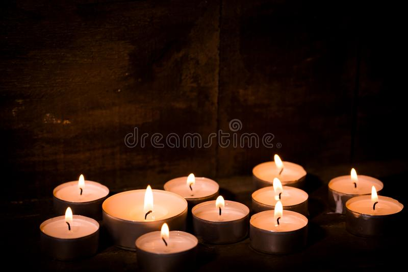Tealight candles on dark wooden background. Group of burning tealight candles on dark wooden background, close-up royalty free stock image