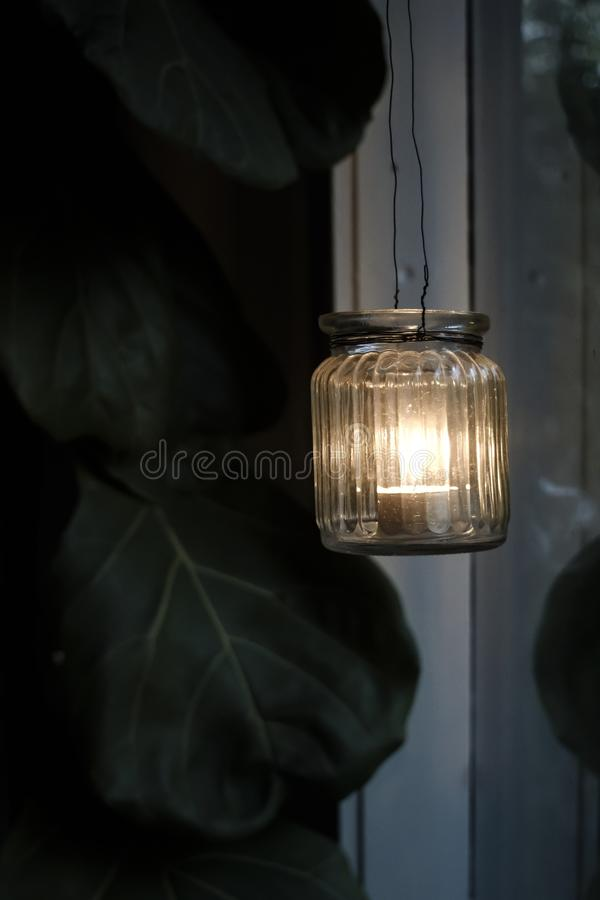 Tealight candlestick at dusk. In a window. Violin fig leaves in the background stock image