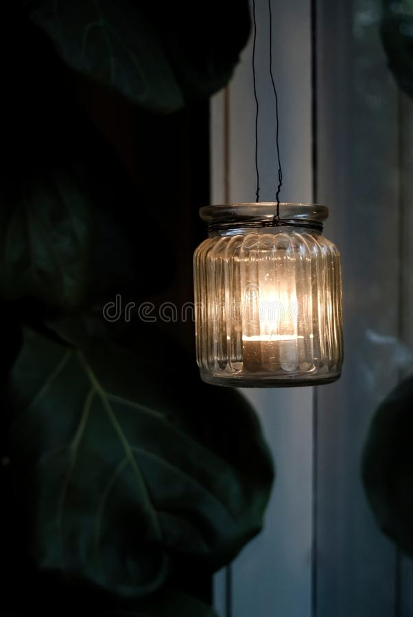 Tealight candlestick at dusk. Tealight candlestick hanging in window at dusk stock photos