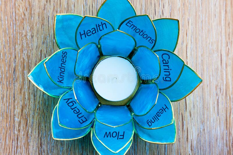 Tealight holder with petals with positive messages and words. Positive and Holistic Messages - Tealight holder with petals with positive messages and words royalty free stock photo