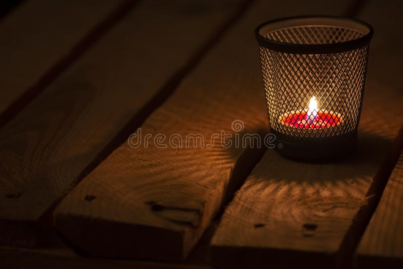 Tealight on wooden background. Candle light on natural wooden background. Red tealight. Cold mood. Soft focus stock photo