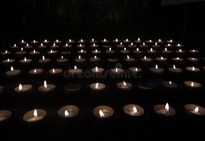 Tealights de prière dans l'obscurité photos stock