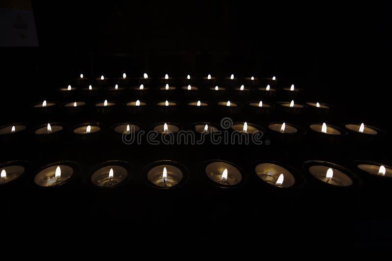 Tealights de prière dans l'obscurité photo stock