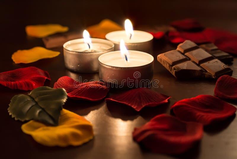 3 Tealights romântico com chocolate e Rose Petals foto de stock