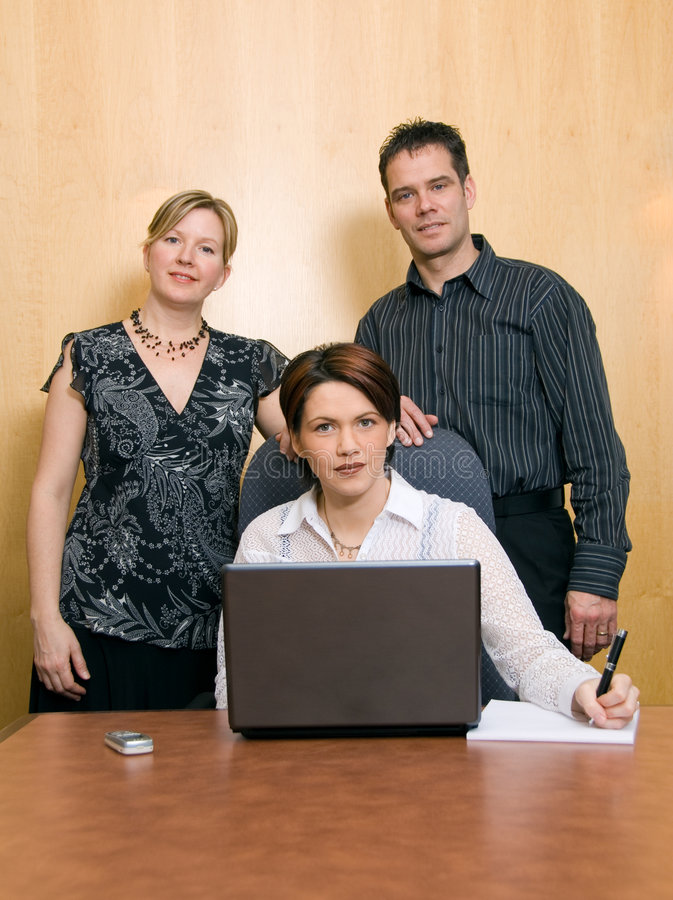 The team. Serious colleagues in an office with a laptop royalty free stock photos