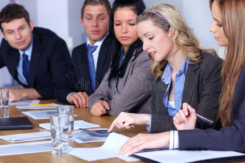 Team of 5 business people work on calculations stock photography