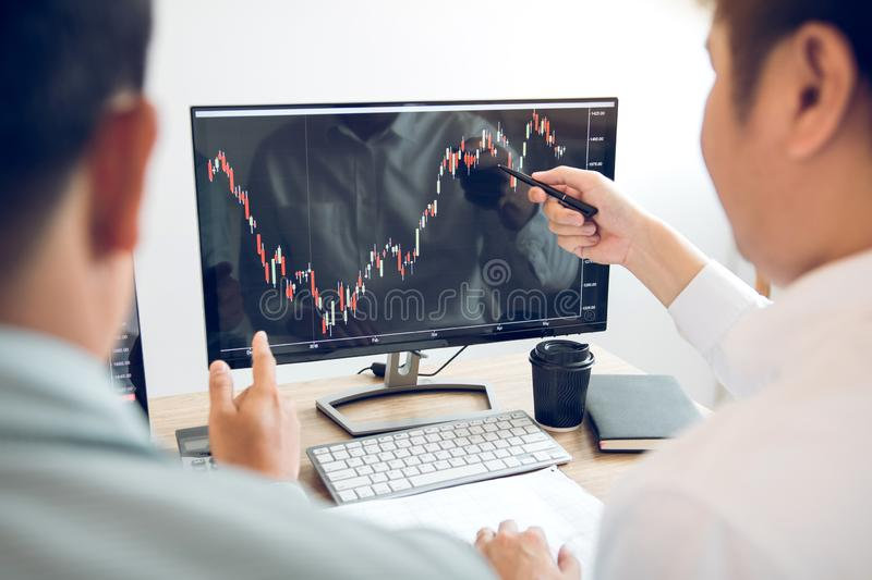 Team of agent trading business people pointing graph and analysis stock market on computer screen in office royalty free stock photo