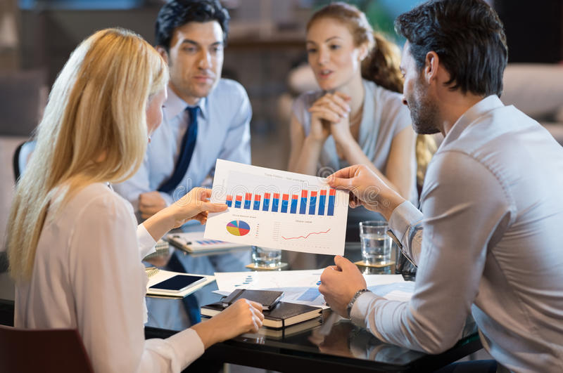 Team analyze annual report. Rear view of business people analyse annual repport with progress charts. Young professional businesspeople looking at policy plans stock image