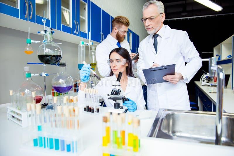 Team arbete av tre uppfinnare i den stängda militära hemliga labbet, flicka royaltyfri bild