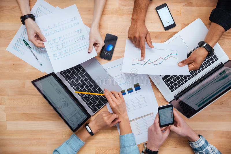 Team arbete för finansiell rapport genom att använda bärbara datorer och smartphones arkivfoto