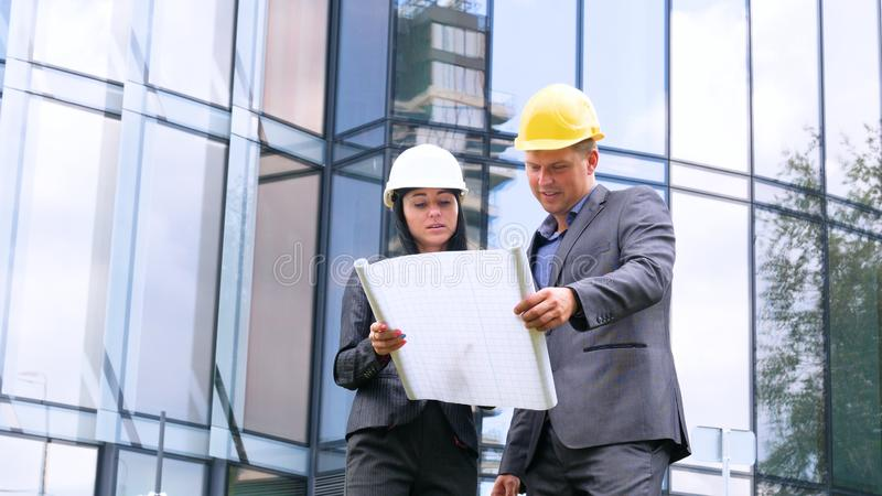 Team of architects and engineer in group on construciton site check documents and business workflow. Engineer inspection in workpl. Ace for architectural plan royalty free stock photos