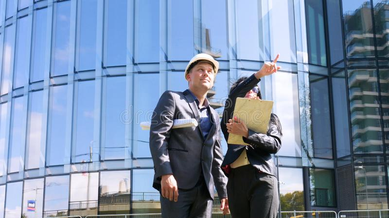 Team of architects and engineer in group on construciton site check documents and business workflow. Engineer inspection in workpl. Ace for architectural plan stock photography
