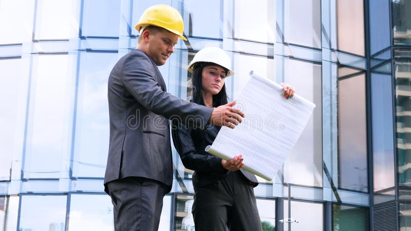 Team of architects and engineer in group on construciton site check documents and business workflow. Engineer inspection in workpl. Ace for architectural plan royalty free stock photo
