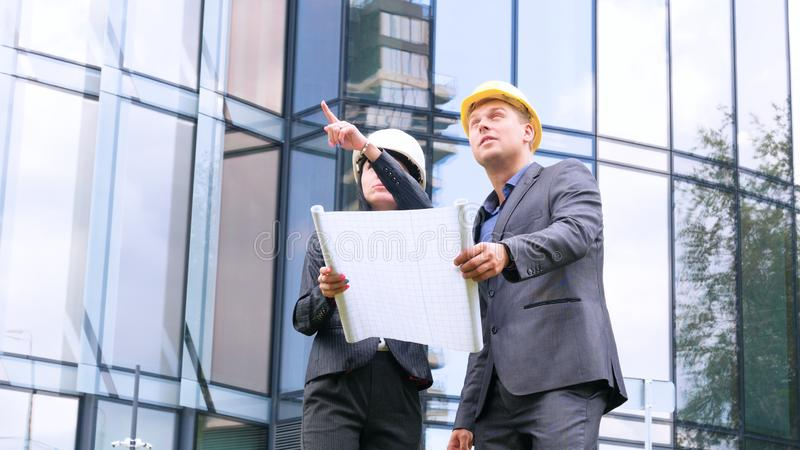 Team of architects and engineer in group on construciton site check documents and business workflow. Engineer inspection in workpl. Ace for architectural plan stock photo
