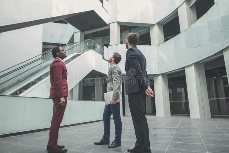 Team of architects work. Wide angle shot of real estate agent with potential clients inside an empty office space royalty free stock images
