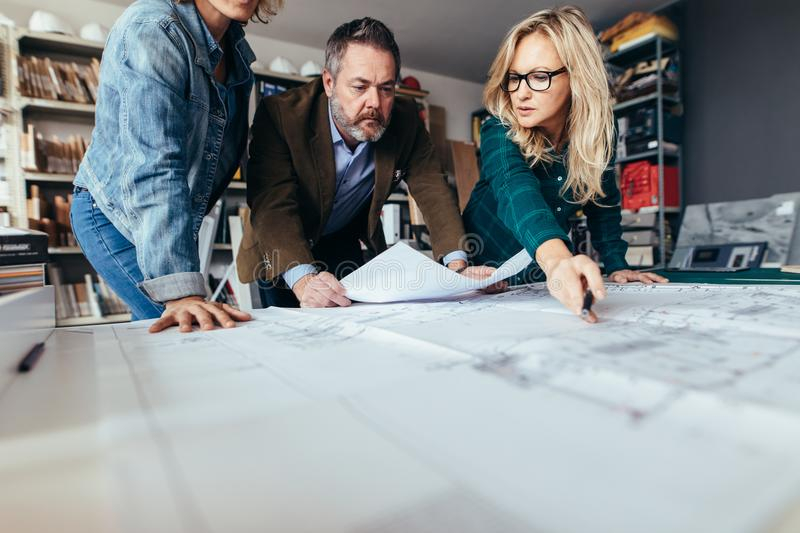 Team of architects working on construction drawing stock photos